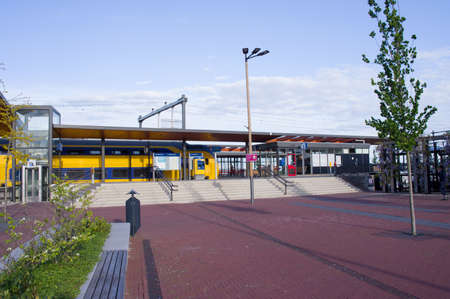 Elst, Netherlands - April 30, 2020: Station Elst, with a moving train in the background