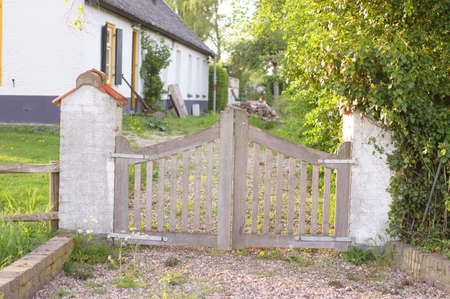 Closed gate that gives access to a path to a green meadow