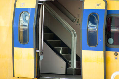 Closeup of a train waiting at platform, with open doors