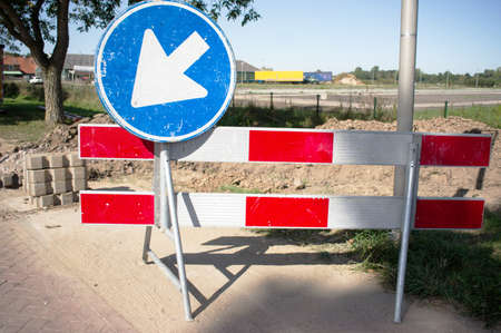 Barriers with blue arrow sign for roadworks Imagens