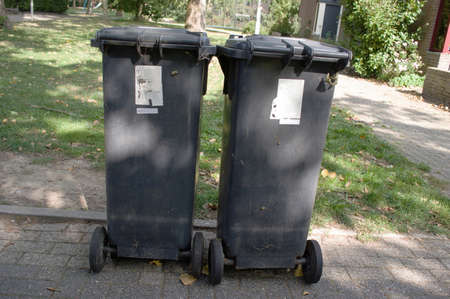 Two gray containers along the street for plastic waste