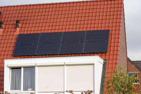 Solar panels on a red roof with dormer for electric power generation