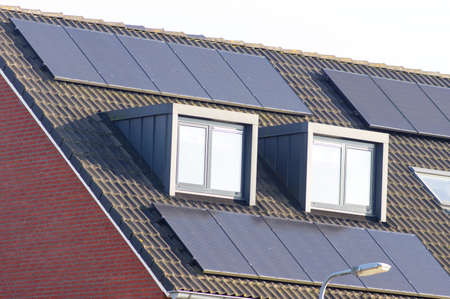 Solar panels on a brown roof with dormer for electric power generation Stock Photo