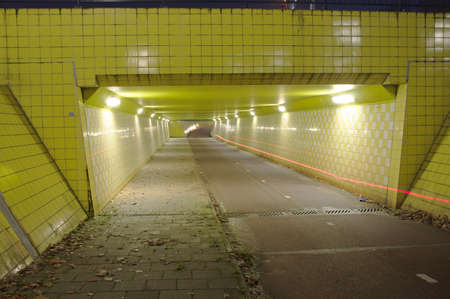 Illuminated yellow tunnel at night with a red trace of a light of a bicycle in Arnhem, Netherlands Stockfoto