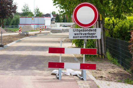 Road closed with barriers for roadworks. Translation: Except, work traffic, residents