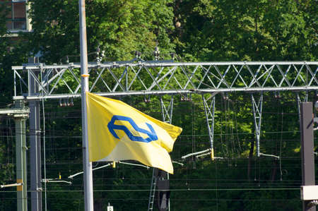 Arnhem, Netherlands - June 2, 2021: The yellow flag of the dutch railways, called the NS, waving in the wind