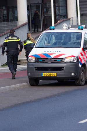Nijmegen, Netherlands - January 14, 2020: Dutch police officers walking away from a police car Redactioneel