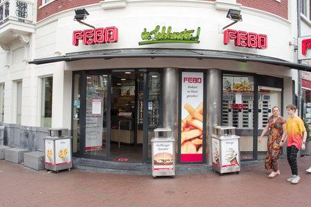 Nijmegen, Netherlands - June 26, 2021: Entrance of a FEBO snack bar with people in Nijmegen. FEBO is a chain of Dutch walk-up fast food restaurants. Redactioneel
