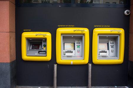 Nijmegen, Netherlands - June 26, 2021: Yellow money measure machines in a row,a dutch ATM banking machine, translation: geldmaat means money measure Redactioneel