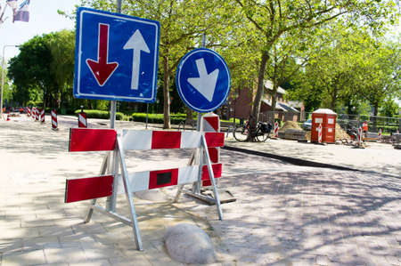 Barriers with blue arrow signs for roadworks Stockfoto