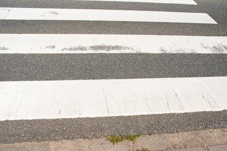Closeup of a pedestrian crossing on a black asphalt road Stockfoto