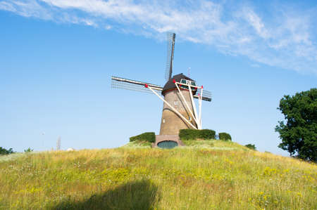 Traditional historic windmill on a green hill in the center of Wijchen in the Netherlands