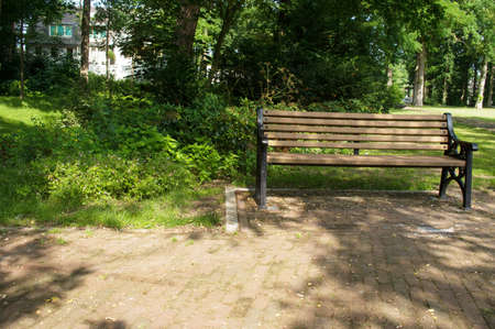 Brown wooden bench in a shady spot in the park in the Netherlands