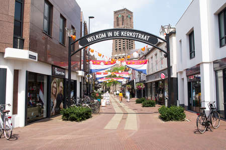Oss, Netherlands - July 9, 2021: Shopping street with people shopping with dutch and orange flags