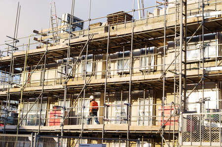 Arnhem, Netherlands - January 8, 2021: Scaffolding of a building under construction with an worker at work