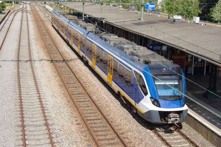 Blue and white train waiting at platform, viewed from above, at station Dieren in the Netherlands