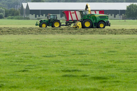 Elst, Netherlands - August 13, 2021:Farmer on tractor and combine harvester to harvest grass