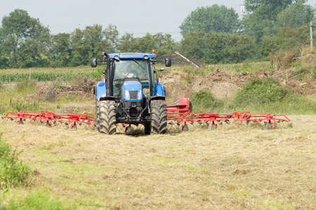 Arnhem, Netherlands - August 13, 2021:Farmer on a tractor is busy on the land in a field with mowed grass Redactioneel