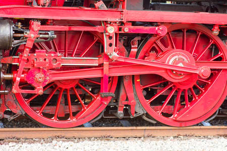 Red wheels of an old historic steam train with mechanics Stockfoto