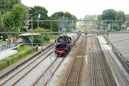 Dieren, Netherlands - August 23, 3021: Historic black steam locomotive arrives at Dieren station in the Netherlands