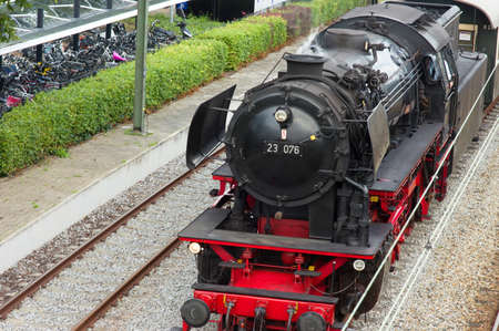 Old historic steam black locomotive with red wheels at station Dieren in the Netherlands Stockfoto