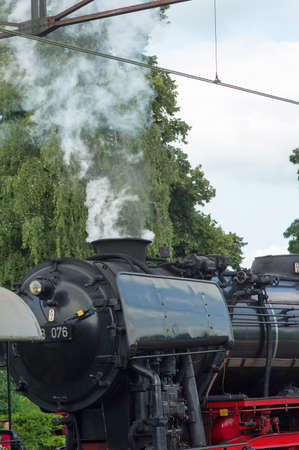 Detail of a old historic steam black locomotive with smoke at station Dieren in the Netherlands