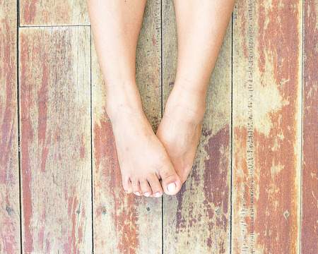 foot spa: Female feet on a wooden floor Stock Photo