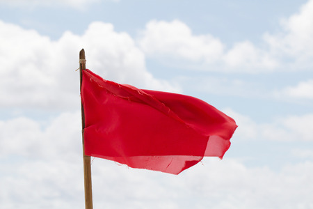 gusty: Red warning flag on a beach with a storm warning flag.