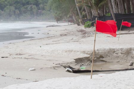 rescue people: Red warning flag on a beach with a storm warning flag.
