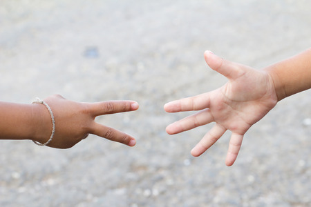 childrens playing: Childrens hands playing, paper and scissors game. Stock Photo