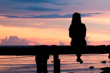 mujer sola: Mujer sola que se sienta en un puente de la puesta del sol de madera. shadows.silhouette estilo abstracto