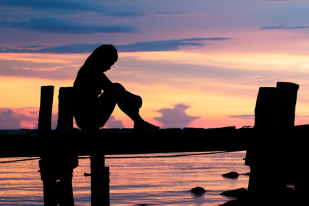 Lonely woman sitting on a wooden bridge sunset. style abstract shadows.silhouette