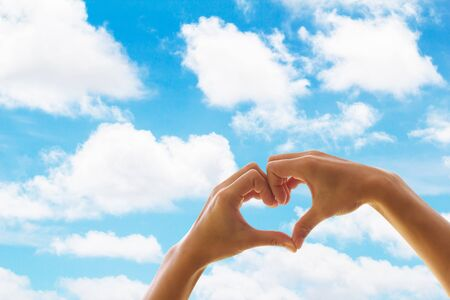 shaped hands: Heart shaped hands on a background of clouds and sky, showing love. Stock Photo