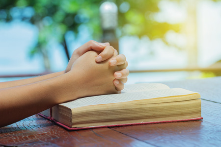 Woman hand placed on a Bible prayer vigil.Religious Reading and stay calm Stock Photo