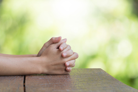 Hands on an old wooden table Natural background blurred bokeh pretty bright. Prayer to God Banque d'images