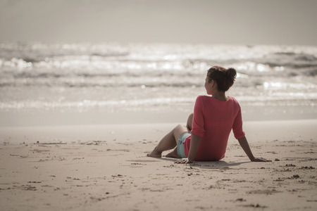 lovelorn: Lovely lady sitting alone on the sand. lonely lovelorn women sit on the beach.Style loneliness.divorce