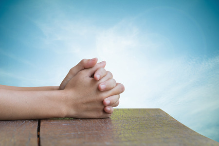 arrepentimiento: Hands on an old wooden table Natural background blurred sky pretty bright. Prayer to God. Foto de archivo