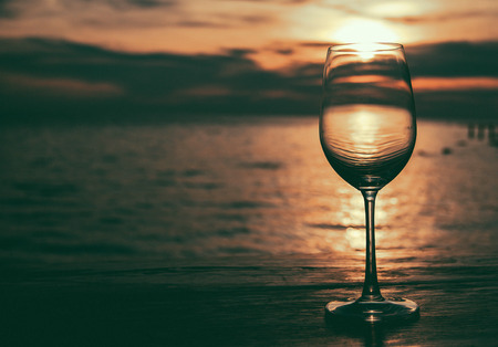friendless: Glass of wine on a wooden table private dinner alone at sunset. Style Darke tone
