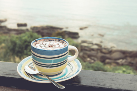 Hot coffee cappuccino on the wooden terrace have sea natural blurred background. Vintage-style colors.