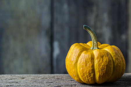 Pumpkin Fingers on a Wood Table On a blurred wooden board background