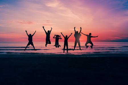 Springende mensen zijn blij om te slagen op het werk. Vrije tijd Reizen in de vakantie Style Silhouette Stockfoto