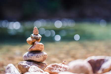 Balanced stone pyramide on shore On a stream of nature Blurred background bokeh