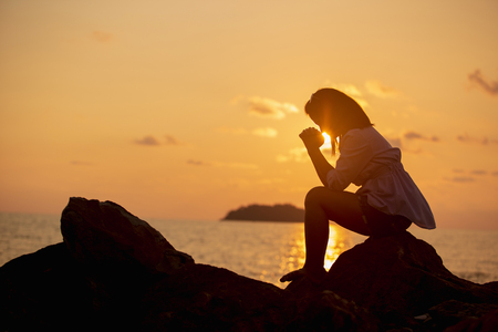 Women praying on ocean landscapes. background during sunset time Hope concept 免版税图像