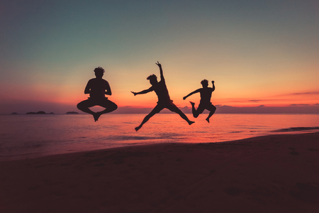 Jumping people are happy to succeed at work. Leisure Travel in the holiday Style Silhouette Stock Photo