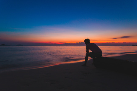 Man alone lonely by the ocean. At the time the sun Stock Photo