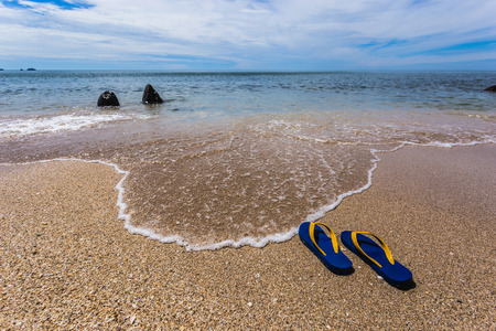 Ocean landscape and sandals on the beach. Welcome summer