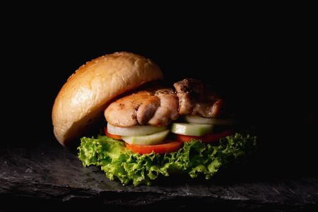 Chicken burgers served with cucumber, tomato, lettuce and onion on a black background.Silhouette style Stock Photo