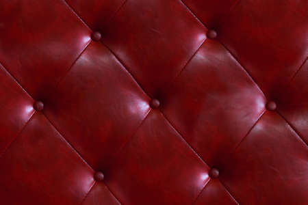 Leather seat or red sofa background Stylish red material decorated with beautiful buttons.
