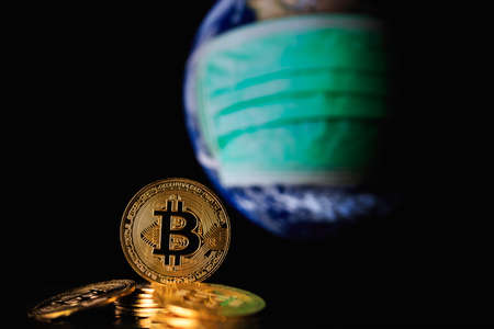 Bitcoin gold coins with blurred background key market figures globe resources and face masks Current concept of viral impact