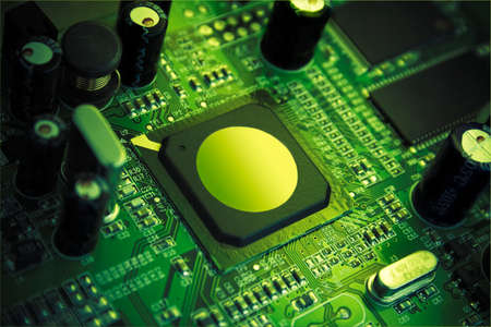 Futuristic high technology chip, surrounded by capacitors, microcircuitry & quartz. Image in beauty green colors, processor pointed by light spot